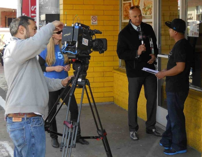 KPBS cameraman films Dwane Brown interviewing Mission Blvd. business owner.