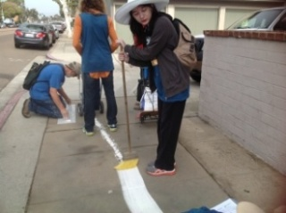 Rachel Eggers spreads and sets the chalk line with a broom.