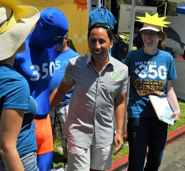 Emily Weir and 350-man usher Todd Gloria into the photo booth, while Masada stands by with a petition and climate-change brochures.