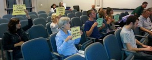 La Mesa residents in the audience hold signs showing support for a strong Climate Action Plan
