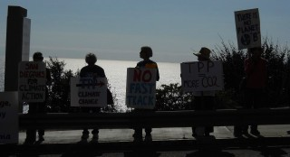 Signholders silhouetted against the ocean.