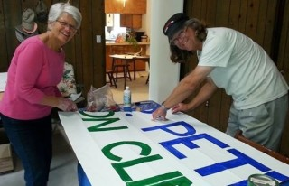 Sue Zesky and Hugh Moore paint a banner with letters large enough that passing drivers can easily see their message.