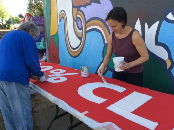 "Jean Costa and Jane Blount paint ""100% clean energy"" onto long red banner."