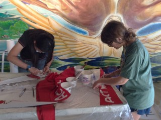 Khanh and Juliet carefully stenciling pennants.